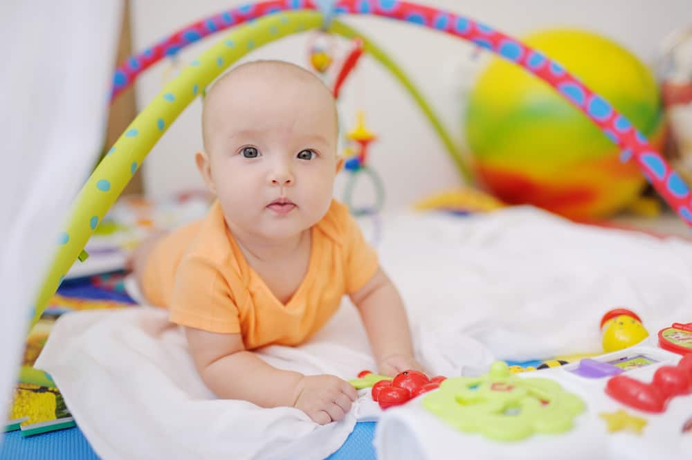 Baby op buik; oefenen met tummy time, kussen en speelgoed om voorkeurshouding te voorkomen. Met spelletjes en speelgoed om te oefenen op de buik- Mamaliefde.nl